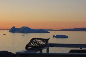 Bucht mit Eisbergen und Festland am Horizont unter orangefarbenem Himmel