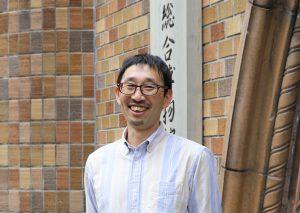 Lächelnder Japaner vor einer Wand aus bunten Ziegeln