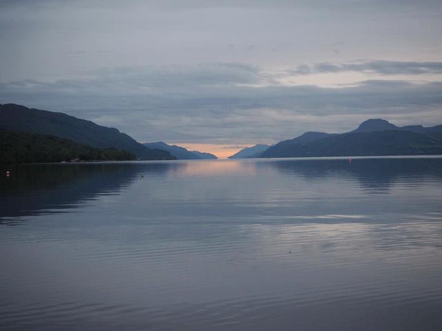 das letzte Licht über einem See unter tief hängenden Wolken