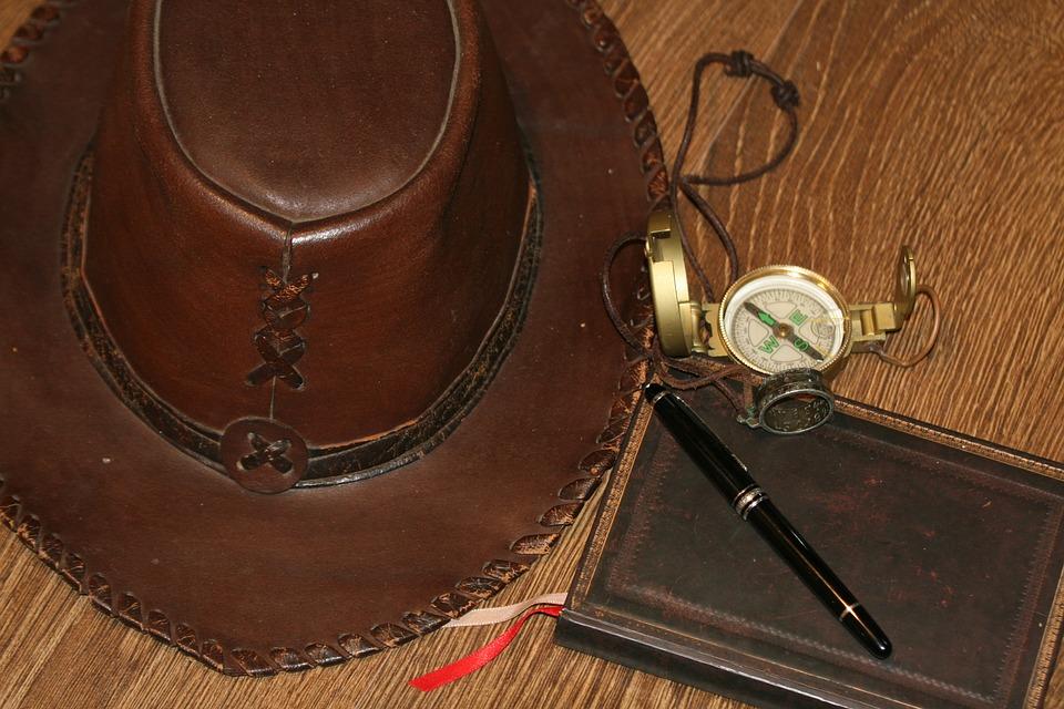 Arrangement aus Lederhut, Kompass und Notizbuch