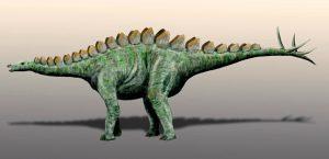 Grünlicher Dinosaurier, der auf vier Beinen läuft, zahlreiche Knochenplatten auf dem Rücken und vier Dornen auf der Schwanzspitze hat