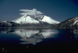 Ein schneebedeckter Berg mit einem deutlichen Krater vor einem blauen See