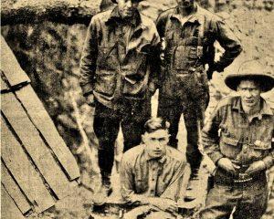 Vergilbte Fotoaufnahme von vier Männern, die an einer Bretterhütte stehen