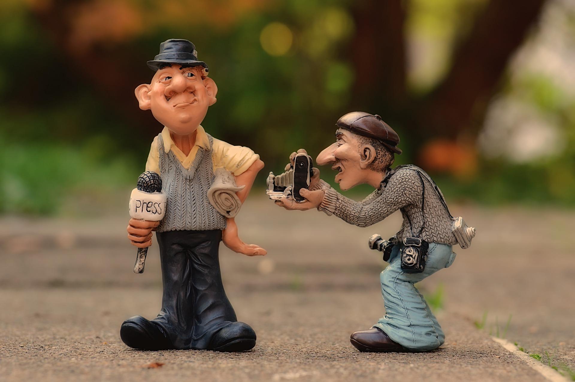 Zwei lustige Gummifiguren, ein Fotograf und ein Journalist